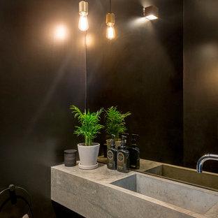 Ispirazione per un piccolo bagno di servizio industriale con WC sospeso, piastrelle nere, piastrelle a specchio, pareti nere, pavimento in cemento, lavabo a consolle, top in cemento e pavimento grigio