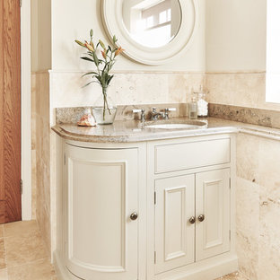 This is an example of a traditional cloakroom in Wiltshire with recessed-panel cabinets, beige cabinets, beige tiles, beige walls, a submerged sink and beige floors.