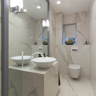 This is an example of a small contemporary cloakroom in London with a wall mounted toilet, porcelain tiles and porcelain flooring.