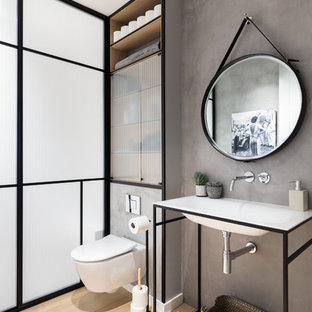 This is an example of a contemporary cloakroom in London with a wall mounted toilet, grey walls, light hardwood flooring, an integrated sink, glass-front cabinets and beige floors.