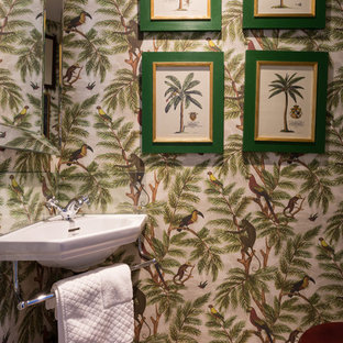 Photo of a small tropical powder room in London with light hardwood floors, a wall-mount sink, beige floor and multi-coloured walls.