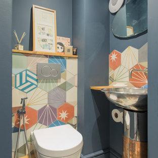 ロンドンのインダストリアルスタイルのおしゃれなトイレ・洗面所 (壁掛け式トイレ、マルチカラーのタイル、青い壁、セメントタイルの床、オーバーカウンターシンク、木製洗面台、マルチカラーの床、ブラウンの洗面カウンター) の写真