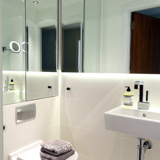 Photo of a contemporary cloakroom in London with a wall-mounted sink, a wall mounted toilet and beige tiles.