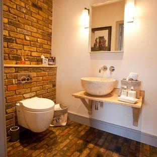 Ispirazione per un grande bagno di servizio design con consolle stile comò, WC sospeso, piastrelle beige, pareti beige, pavimento in mattoni, lavabo sospeso, top in legno e pavimento rosso
