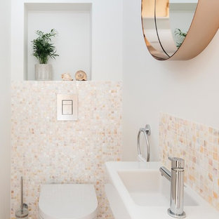 Small traditional cloakroom in London with a wall mounted toilet, beige tiles, mosaic tiles, white walls, a wall-mounted sink and light hardwood flooring.