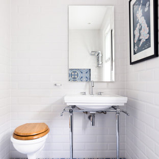 This is an example of a classic cloakroom in London with white tiles, metro tiles, a console sink and blue floors.