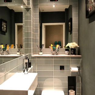 This is an example of a small modern cloakroom with a one-piece toilet, grey tiles, ceramic tiles, grey walls, dark hardwood flooring, a wall-mounted sink, wooden worktops, brown floors and grey worktops.