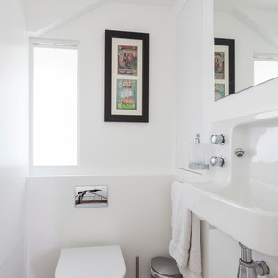 Example of a small trendy dark wood floor powder room design in London with a wall-mount sink and white walls