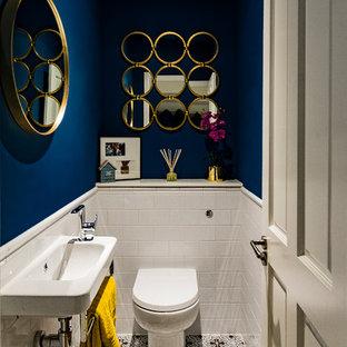 На фото: со средним бюджетом туалеты в современном стиле с унитазом-моноблоком, белой плиткой, синими стенами, полом из цементной плитки, подвесной раковиной и разноцветным полом