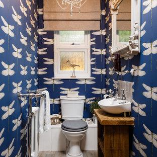 Stilmix Gästetoilette mit verzierten Schränken, dunklen Holzschränken, blauer Wandfarbe, Laminat, Wandwaschbecken, Waschtisch aus Holz, Wandtoilette mit Spülkasten, grauen Fliesen, grauem Boden und brauner Waschtischplatte in Cambridgeshire