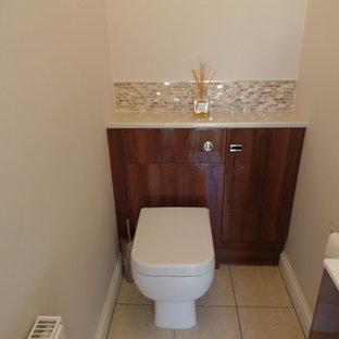 Cette photo montre un petit WC et toilettes moderne avec un placard à porte plane, un plan de toilette en stratifié, un mur beige et carrelage en mosaïque.