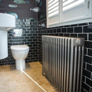 Пример оригинального дизайна: маленький туалет в современном стиле с унитазом-моноблоком, черной плиткой, стеклянной плиткой, черными стенами, полом из известняка, подвесной раковиной и бежевым полом