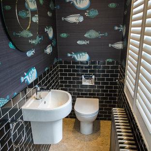 Неиссякаемый источник вдохновения для домашнего уюта: маленький туалет в современном стиле с унитазом-моноблоком, черной плиткой, стеклянной плиткой, черными стенами, полом из известняка, подвесной раковиной и бежевым полом