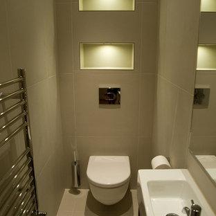 Пример оригинального дизайна: маленький туалет в современном стиле с консольной раковиной, плоскими фасадами, темными деревянными фасадами, инсталляцией, бежевой плиткой, керамогранитной плиткой, серыми стенами, полом из керамогранита и серым полом