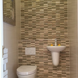Photo of a small contemporary cloakroom in West Midlands with a one-piece toilet, beige tiles, porcelain tiles, beige walls, porcelain flooring and a wall-mounted sink.