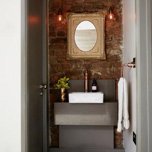 ロンドンのエクレクティックスタイルのおしゃれなトイレ・洗面所 (淡色無垢フローリング、レンガ壁) の写真