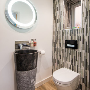 Inspiration for a small modern cloakroom in West Midlands with a wall mounted toilet, multi-coloured tiles, matchstick tiles, beige walls, medium hardwood flooring, a pedestal sink and brown floors.