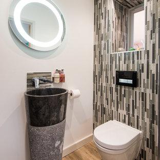 Ejemplo de aseo minimalista, pequeño, con sanitario de pared, baldosas y/o azulejos multicolor, azulejos en listel, paredes beige, suelo de madera en tonos medios, lavabo con pedestal y suelo marrón