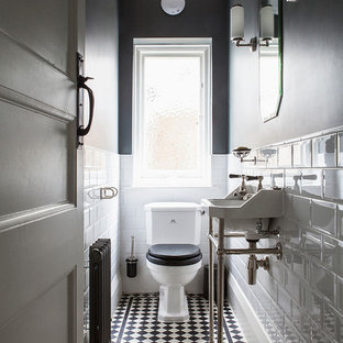 Inspiration for a small classic cloakroom in Sussex with grey walls, porcelain flooring, black and white tiles, white tiles, a console sink, a two-piece toilet and multi-coloured floors.
