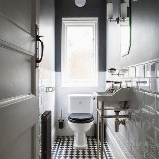 Cette image montre un petit WC et toilettes traditionnel avec un mur gris, un sol en carrelage de porcelaine, un carrelage noir et blanc, un carrelage blanc, un plan vasque, un WC séparé et un sol multicolore.