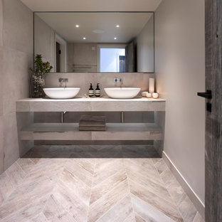 Design ideas for a medium sized contemporary cloakroom in Cheshire with a wall mounted toilet, grey tiles, porcelain tiles, grey walls, porcelain flooring, a trough sink, tiled worktops, grey floors and grey worktops.