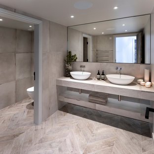Photo of a medium sized contemporary cloakroom in Cheshire with a wall mounted toilet, grey tiles, porcelain tiles, grey walls, porcelain flooring, a trough sink, tiled worktops, grey floors and grey worktops.