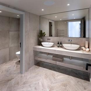 Exemple d'un WC et toilettes tendance de taille moyenne avec un WC suspendu, un carrelage gris, des carreaux de porcelaine, un mur gris, un sol en carrelage de porcelaine, une grande vasque, un plan de toilette en carrelage, un sol gris et un plan de toilette gris.