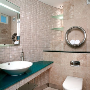 Small contemporary cloakroom in Dorset with open cabinets, a wall mounted toilet, beige tiles, beige walls, a vessel sink, beige floors, glass worktops and turquoise worktops.