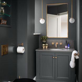 Klassisk inredning av ett mellanstort grå grått toalett, med en toalettstol med hel cisternkåpa, ljust trägolv, bänkskiva i kalksten, luckor med infälld panel, grå skåp, grå väggar, ett undermonterad handfat och beiget golv