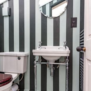 Réalisation d'un petit WC et toilettes bohème avec un placard en trompe-l'oeil, des portes de placards vertess, un WC à poser, un mur vert, un sol en contreplaqué, un lavabo de ferme et un sol vert.