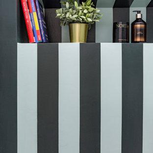 Eklektisk inredning av ett litet toalett, med möbel-liknande, gröna skåp, en toalettstol med hel cisternkåpa, gröna väggar, plywoodgolv, ett piedestal handfat och grönt golv