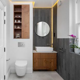 Diseño de aseo nórdico con armarios con paneles lisos, puertas de armario de madera oscura, sanitario de pared, baldosas y/o azulejos grises, paredes blancas, lavabo sobreencimera, suelo gris y encimeras blancas