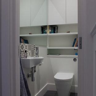 ロンドンの小さいコンテンポラリースタイルのおしゃれなトイレ・洗面所 (壁掛け式トイレ、マルチカラーのタイル、テラコッタタイル、白い壁、磁器タイルの床、壁付け型シンク、グレーの床) の写真