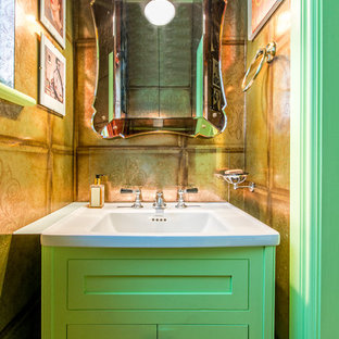 Small eclectic cloakroom in London with green cabinets and an integrated sink.