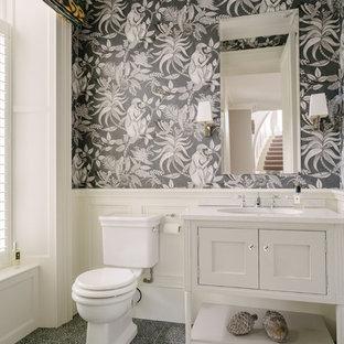 Idée de décoration pour un petit WC et toilettes tradition avec des portes de placard blanches, un sol en carrelage de porcelaine, un sol bleu, un placard à porte affleurante, un mur noir, un lavabo encastré et un plan de toilette blanc.