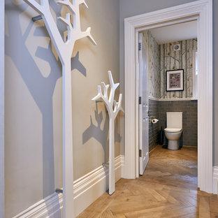 На фото: большой туалет в стиле фьюжн с унитазом-моноблоком, серой плиткой, плиткой кабанчик, серыми стенами и паркетным полом среднего тона с