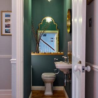 Cette photo montre un petit WC et toilettes chic avec un WC à poser, un mur vert, un sol en bois brun, un lavabo suspendu et un sol marron.