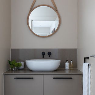 Photo of a small contemporary cloakroom in Hertfordshire with quartz worktops, flat-panel cabinets, grey cabinets, grey walls, a vessel sink, grey floors and grey worktops.