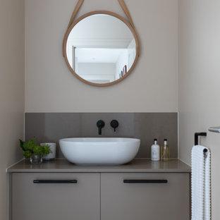 Imagen de aseo contemporáneo, pequeño, con encimera de cuarcita, armarios con paneles lisos, puertas de armario grises, paredes grises, lavabo sobreencimera, suelo gris y encimeras grises