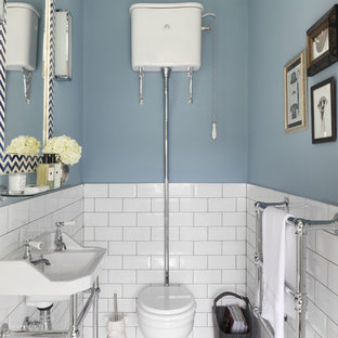 Inspiration for a small traditional cloakroom in London with a two-piece toilet, white tiles, blue walls, marble flooring, metro tiles and a console sink.