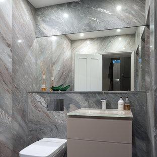 Réalisation d'un WC et toilettes design de taille moyenne avec un placard à porte plane, un WC à poser, un carrelage beige, des dalles de pierre, un mur beige, un sol en marbre, un lavabo posé et un plan de toilette en verre.