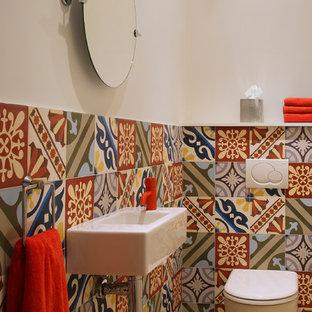 Small mediterranean cloakroom in London with a wall-mounted sink, multi-coloured tiles, multi-coloured walls, porcelain flooring and a one-piece toilet.