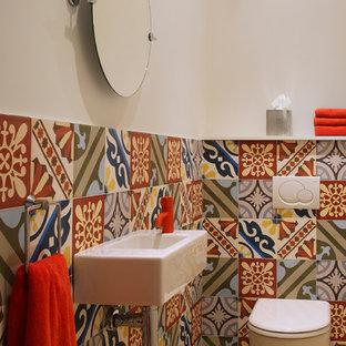 Réalisation d'un petit WC et toilettes méditerranéen avec un lavabo suspendu, un carrelage multicolore, un mur multicolore, un sol en carrelage de porcelaine et un WC à poser.