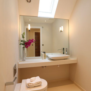 This is an example of a large contemporary cloakroom in London with solid surface worktops, a wall mounted toilet, beige tiles, porcelain flooring, beige walls and a vessel sink.