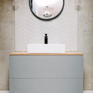 Cette photo montre un WC et toilettes tendance avec un placard à porte plane, des portes de placard grises, un carrelage gris, un mur gris, une vasque et un sol multicolore.