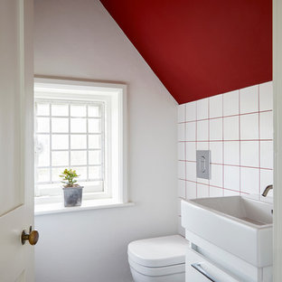 Photo of a contemporary cloakroom in Surrey with flat-panel cabinets, white cabinets, white tiles, white walls, a console sink and black floors.