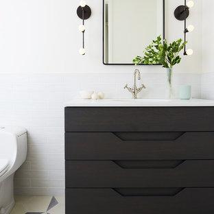 Idées de décoration pour des WC et toilettes nordiques avec un placard en trompe-l'oeil, des portes de placard noires, un mur blanc, un sol multicolore et un plan de toilette blanc.