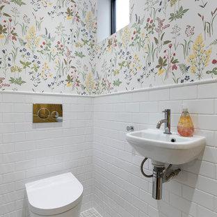 Esempio di un bagno di servizio tradizionale con WC sospeso, pareti multicolore, lavabo sospeso e pavimento bianco