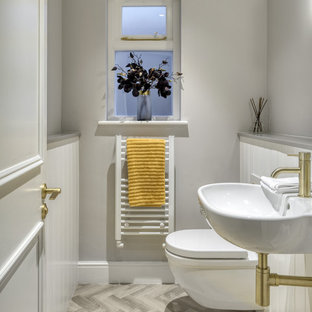 Photo of a classic cloakroom in London with a wall mounted toilet, grey walls, a wall-mounted sink and grey floors.