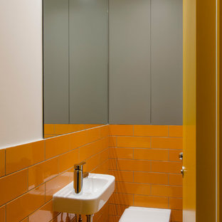 Photo of a small modern cloakroom in London with flat-panel cabinets, grey cabinets, a wall mounted toilet, orange tiles, ceramic tiles, orange walls, ceramic flooring and a wall-mounted sink.
